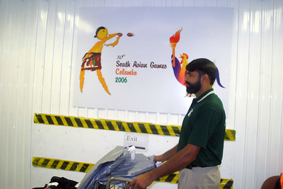 Farasatleaving the terminal with the South Asian Games logo behind him.