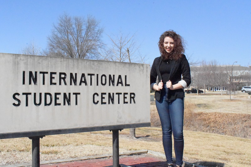 Kansas State University international student,  Mary Abounabhan posing in front of the international student center  (Skylar Stephens | Collegian Media Group)