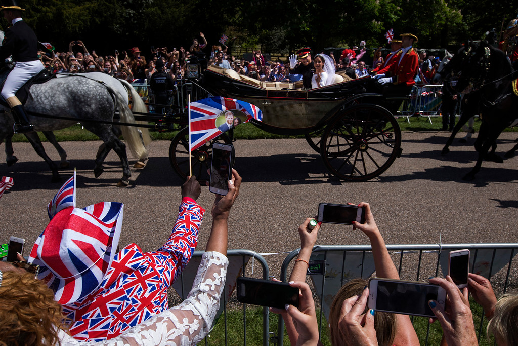 . Britain\'s Prince Harry and Meghan Markle wave to the crowd in a carriage after their wedding ceremony at St. George\'s Chapel in Windsor Castle in Windsor, near London, England, Saturday, May 19, 2018. (AP Photo/Emilio Morenatti)