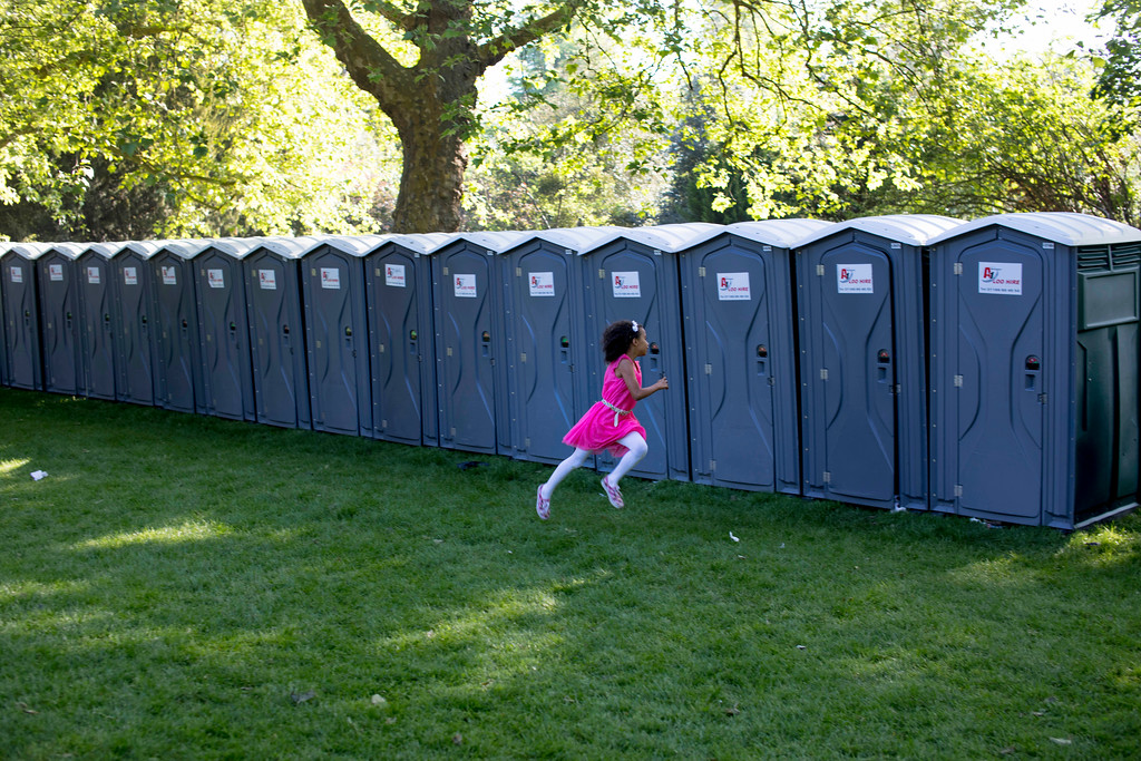 . A girl plays next to a row of portable toilets placed alongside the route the newly wed royal couple will travel, prior to the wedding ceremony of Prince Harry and Meghan Markle at St. George\'s Chapel in Windsor Castle in Windsor, near London, England, Saturday, May 19, 2018. (AP Photo/Peter Dejong)