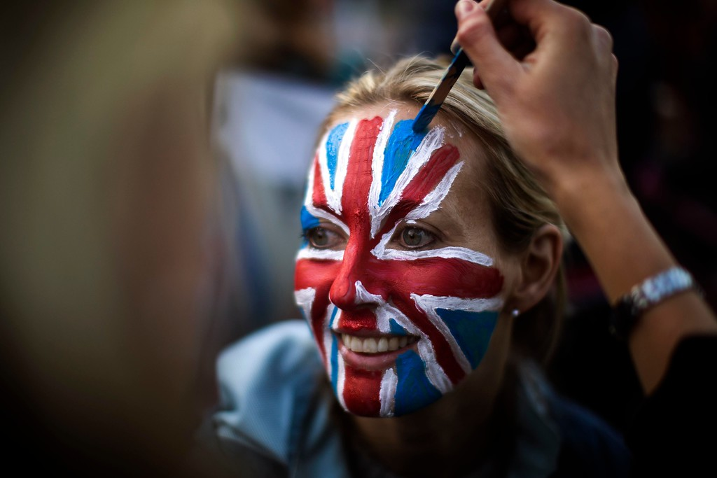 . A woman is painted with a British flag on her face, as they wait at The Long Walk to watch the carriage procession after the wedding of Britain\'s Prince Harry and Meghan Markle at St. George\'s Chapel in Windsor Castle in Windsor, near London, England, Saturday, May 19, 2018. (AP Photo/Emilio Morenatti)