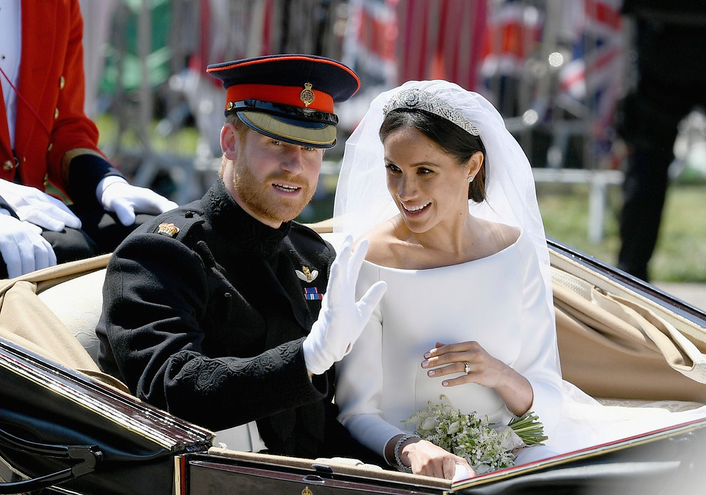 . Meghan Markle reacts as she rides in a carriage with her husband Britain\'s Prince Harry after their wedding ceremony at St. George\'s Chapel in Windsor Castle in Windsor, near London, England, Saturday, May 19, 2018. (Jeff J Mitchell/pool photo via AP)