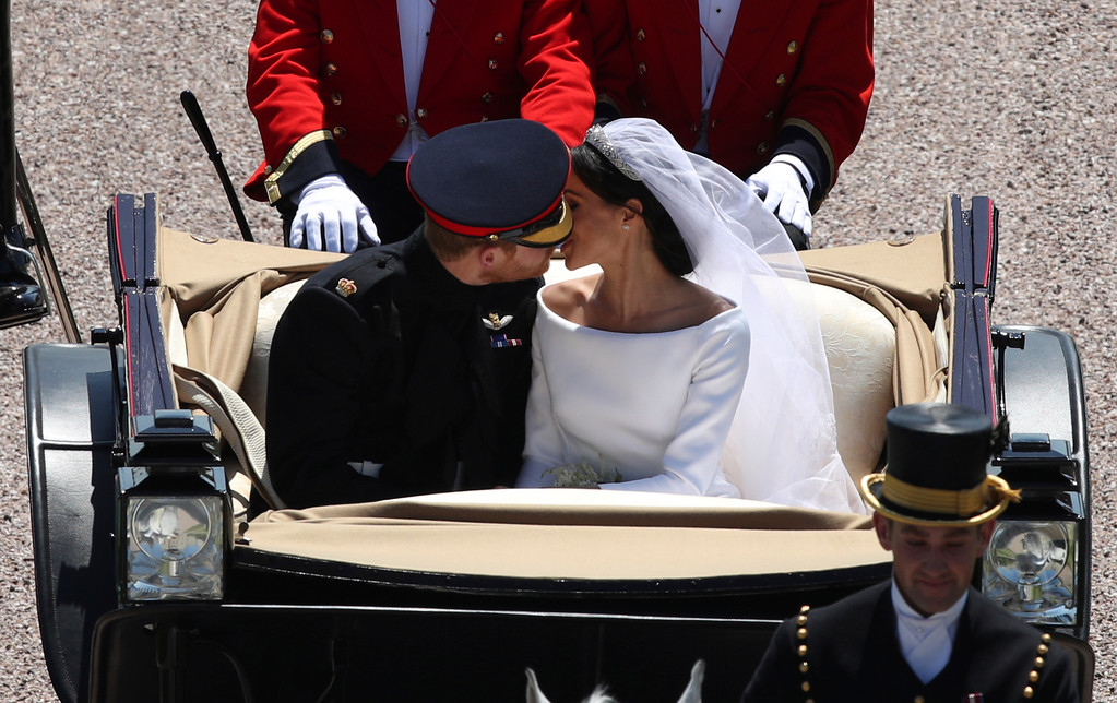 . Britain\'s Prince Harry and Meghan Markle kiss as they ride in a carriage down the Long Walk after their wedding ceremony of Prince Harry and Meghan Markle at St. George\'s Chapel in Windsor Castle in Windsor, near London, England, Saturday, May 19, 2018. (Yui Mok/pool photo via AP)