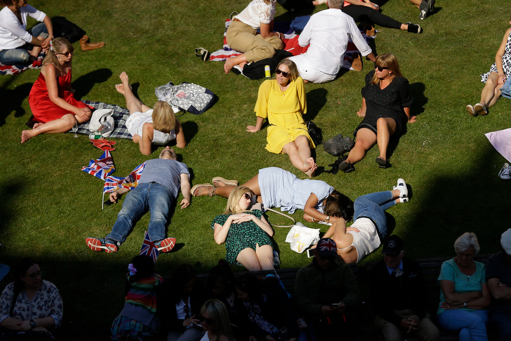 . People relax on a grassy bank outside Windsor Castle after Prince Harry and Meghan Markle\'s wedding ceremony at St. George\'s Chapel in Windsor, near London, England, Saturday, May 19, 2018. (AP Photo/Matt Dunham)