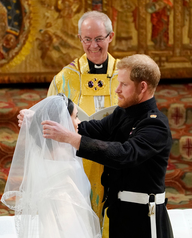 . Britain\'s Prince Harry pulls back the veil of Meghan Markle watched by Archbishop of Canterbury Justin Welby during their wedding at St. George\'s Chapel in Windsor Castle in Windsor, near London, England, Saturday, May 19, 2018. (Owen Humphreys/pool photo via AP)