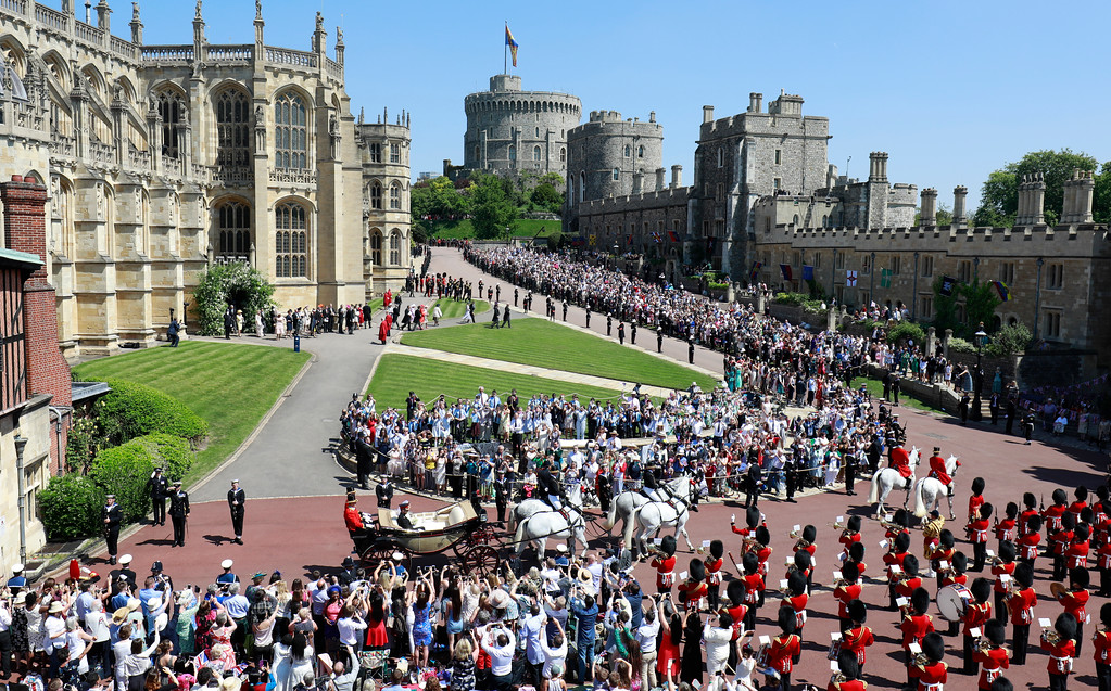 . Well-wishers lining the streets wave and cheer as Britain\'s Prince Harry, Duke of Sussex and his wife Meghan Markle, Duchess of Sussex after their wedding ceremony at St. George\'s Chapel in Windsor Castle in Windsor, near London, England, Saturday, May 19, 2018. (Odd Andersen/pool photo via AP)