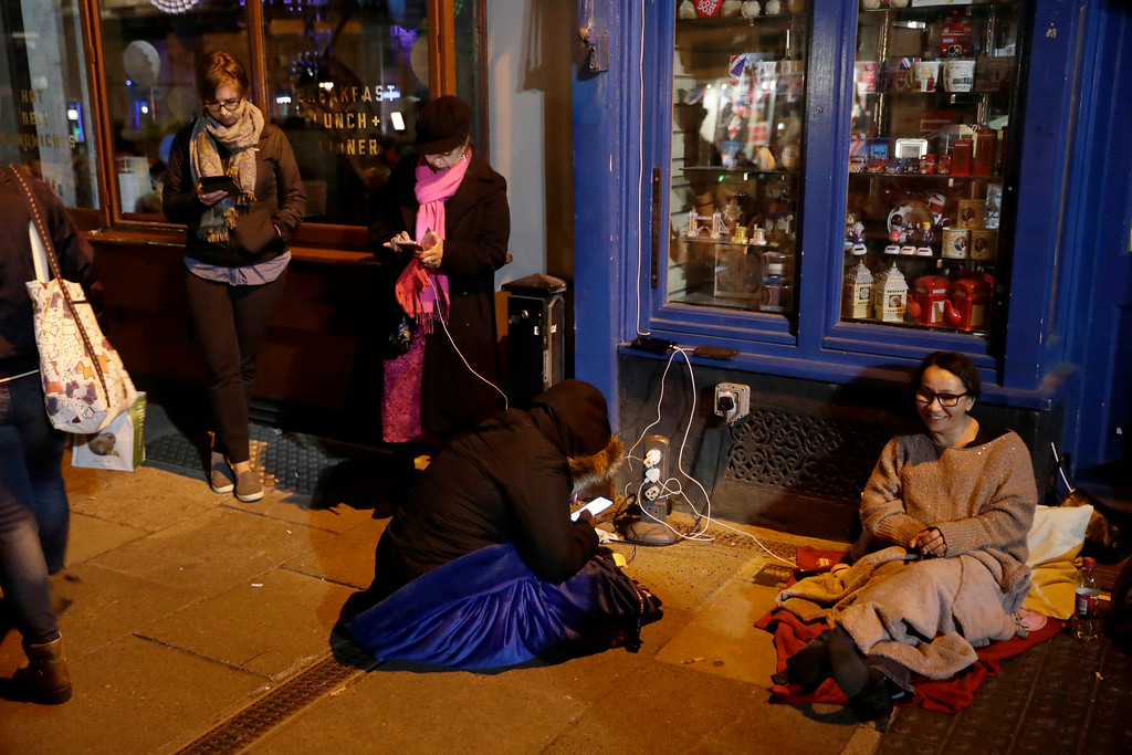 . Before sunrise, royal fans charge phones as they wait to see the carriage procession near Windsor Castle, ahead of the wedding ceremony of Prince Harry and Meghan Markle at St. George\'s Chapel in Windsor, near London, England, Saturday, May 19, 2018. (AP Photo/Matt Dunham)