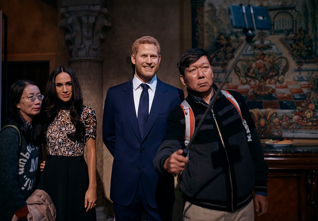 . A couple takes a selfie with wax sculptures of Meghan Markle, second left, and Prince Harry, second right, during a viewing party of the royal wedding of Meghan Markle and Prince Harry of Wales, at the Madame Tussauds wax museum on Saturday, May 19, 2018, in New York. (AP Photo/Andres Kudacki)