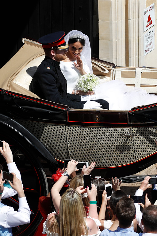 . Britain\'s Prince Harry and Meghan Markle leave in a carriage after their wedding ceremony at St. George\'s Chapel in Windsor Castle in Windsor, near London, England, Saturday, May 19, 2018. (Odd Andersen/pool photo via AP)
