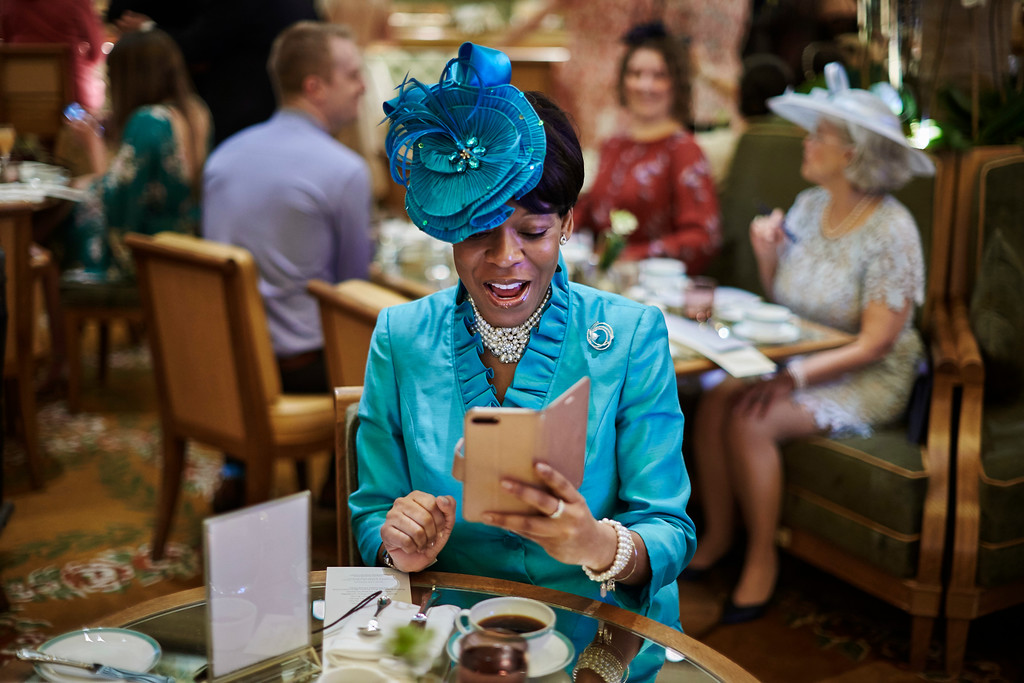 . A woman uses her phone during a viewing party of the royal wedding of Meghan Markle and Prince Harry of Wales, at the Plaza Hotel on Saturday, May 19, 2018, in New York. Prince Harry and Meghan Markle gazed into each other\'s eyes and pledged their eternal love Saturday as they married at St. George\'s Chapel in front of hundreds of celebrity guests and millions of viewers around the world.  (AP Photo/Andres Kudacki)