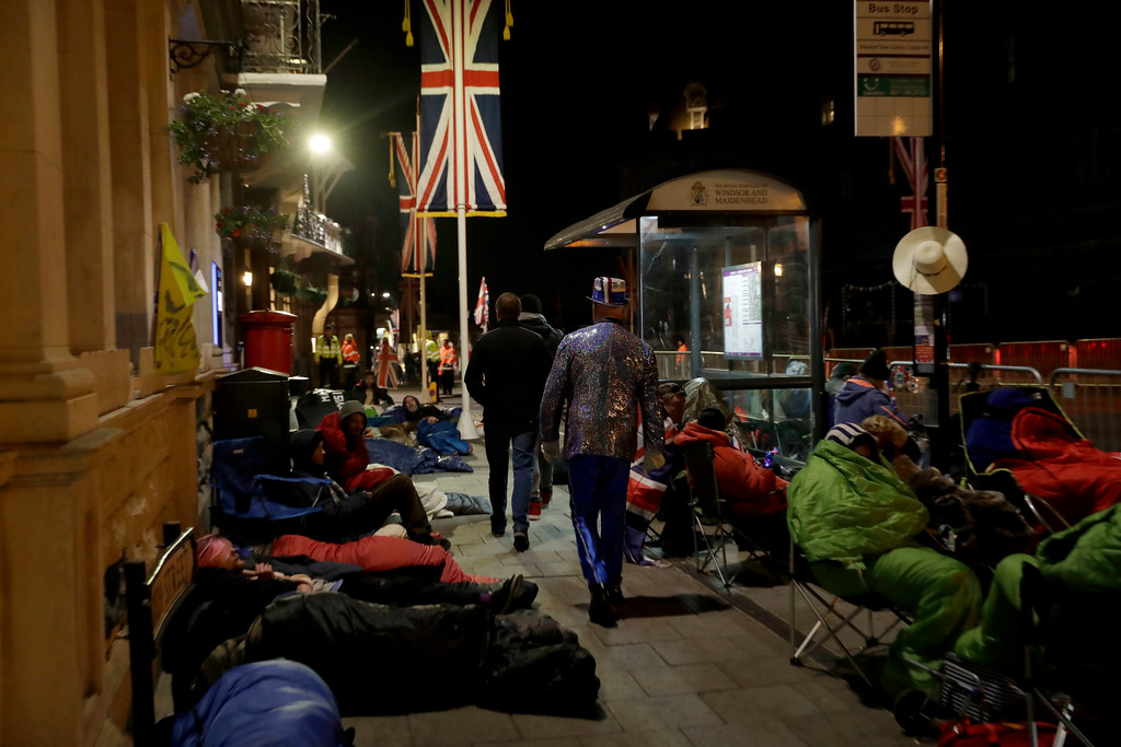 . Before sunrise, royal fans rest and sleep in the street to hold a spot at the front of barriers for the carriage procession outside Windsor Castle, ahead of the wedding ceremony of Prince Harry and Meghan Markle at St. George\'s Chapel in Windsor, near London, England, Saturday, May 19, 2018. (AP Photo/Matt Dunham)