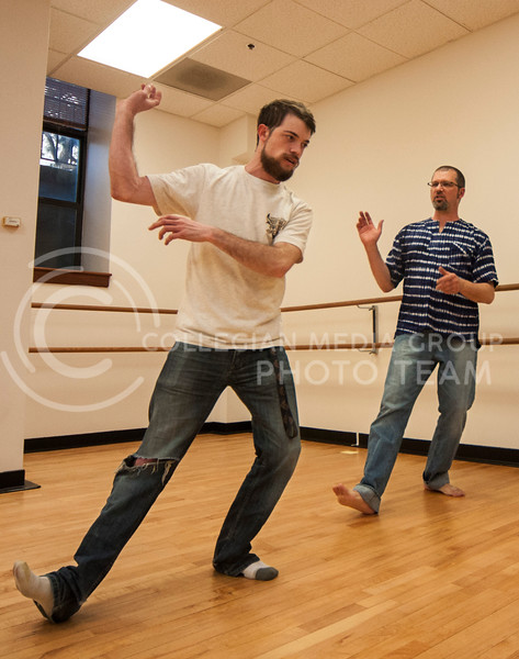 Instructor Neil Dunn works one-on-one with Chris Backman, senior in math, during the African Dance class in Nichols Hall on March 3.