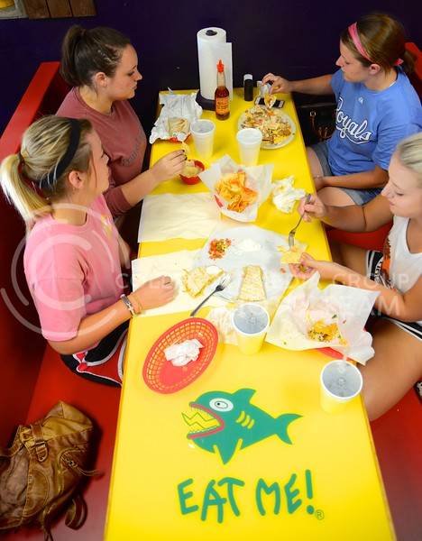 From left to right, Ashley Ladd, junior in life science and pre-vet, Mary Harness, junior in sociology, Claire Finkle, senior in advertising and Kati Krieg, junior in english, enjoy their meal underneath the fish adorning the wall of Fuzzy's Taco Shop Tuesday evening. The restaurant with the funny name recently opened in Aggieville in the property vacated by the Hibachi Hut. Parker Robb | Royal Purple