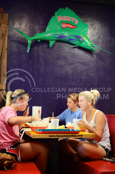 From left to right, Ashley Ladd, junior in life science and pre-vet, Claire Finkle, senior in advertising and Kati Krieg, junior in english, enjoy their meal underneath the fish adorning the wall of Fuzzy's Taco Shop Tuesday evening. The restaurant with the funny name recently opened in Aggieville in the property vacated by the Hibachi Hut. Parker Robb | Royal Purple