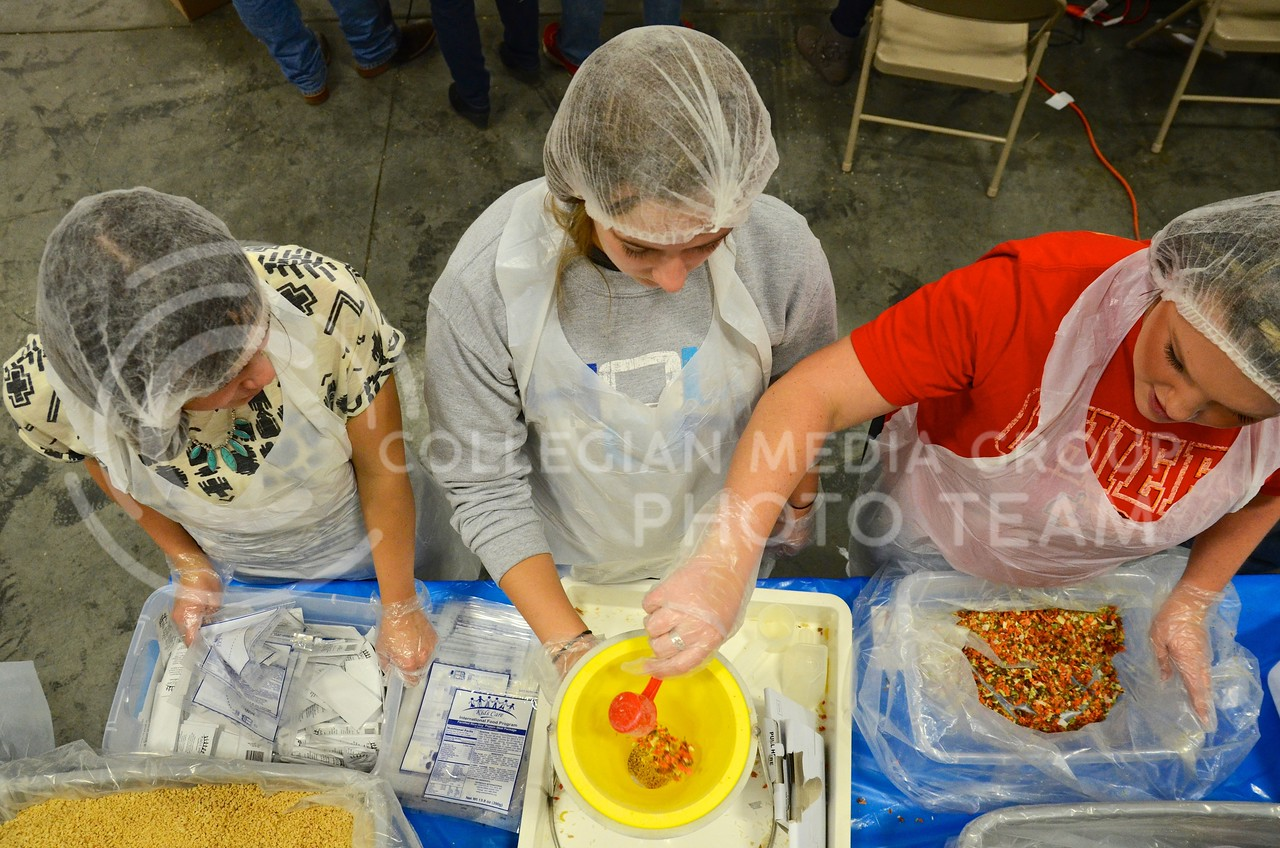Alysa Wendelburg, senior in agribusiness, left, Shannon Maxwell, sophomore in agricultural economics, and Kellie Jackson, senior also in agricultural economics, scoop rice and dried vegetables into a plastic bag at the KSU Hunger Aid food packaging event hosted by Alpha Zeta Sunday afternoon at the National Guard Armory. K-State students worked in several assembly lines packaging 40,000 meals, half to be sent to hungry Kansans, and the other half to be sent to Tanzania.