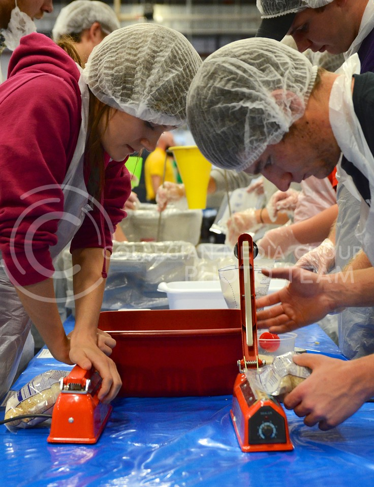 Emma Montgomery, junior in interior architecture and product design, and Nick Wineinger, junior in agribusiness, seal packages of dried soy, vegetables and rice, at the KSU Hunger Aid food packaging event hosted by Alpha Zeta Sunday afternoon at the National Guard Armory.