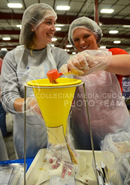 Shannon Maxwell, sophomore in agricultural economics, and Kellie Jackson, senior also in agricultural economics, scoop rice and dried vegetables into a plastic bag at the KSU Hunger Aid food packaging event hosted by Alpha Zeta Sunday afternoon at the National Guard Armory. Alpha Zeta has hosted several other hunger-related events at K-State, including SWIPE Out Hunger food packaging events.