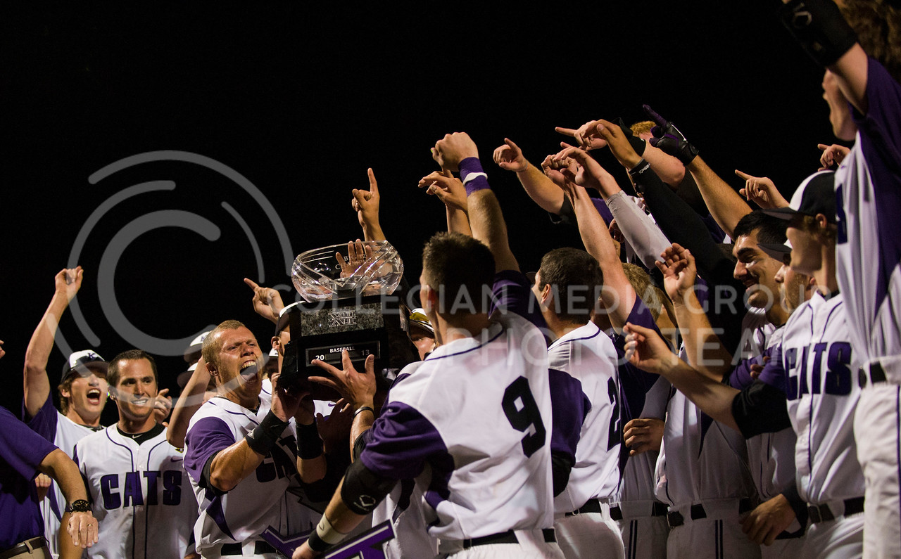 The K-State baseball team yells in excitement as they hoist the Big 12 Championship trouphy after defeating Oklahoma on May 17, 2013.