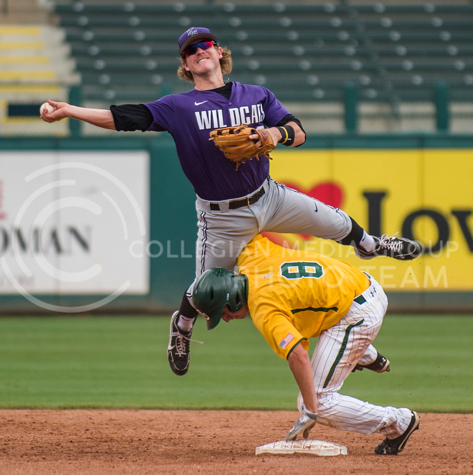 K-State short stop Lance Miles leaps over Baylor second baseman Lawton Langford to throw to first during the 13-9 win over the Bears Friday at Chickasaw Bricktown Ballpark during the Big 12 Championship.  The Wildcats scored five runs in the ninth inning to take and ensure the win that coach Hill hopes will give K-State the chance to host a regional for the NCAA tournament.