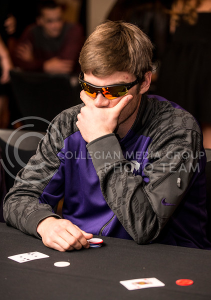 Clayton Dalrymple, sophmore in management, uses sungalsses to mask his expression while playing black jack at the Chi-O Casino at Holiday Inn on Feb. 25.