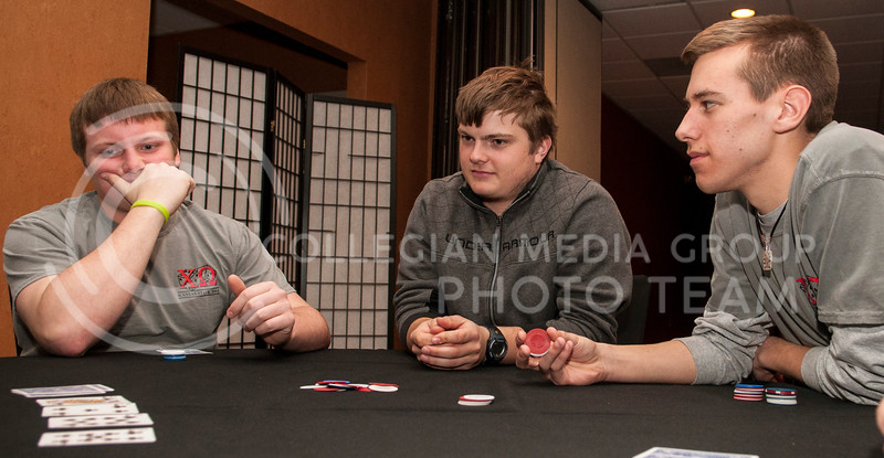 from left: Connor Nace, freshan in kinesiology, considers his options, while Matthew Marshall, freshman in business and Chris Wynn, junior in psychology, wait for their turns to bet or check at the Chi-O Casino at Holiday Inn on Feb. 25.