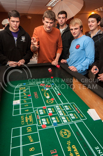 Spencer Bontrager, fifth year senior in industrial engineering, rolls the dice while playing craps at the Chi-O Casino at Holiday Inn on Feb. 25.