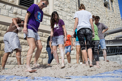 Lauren Karle, a third year graduate student in ceramics, and Andrea Sweetwood, a senior in kinesiology, stomp the clay with other K-students.  The second annual Clay Stomp was held Saturday, Sept. 28, 2013 from 10am to 3pm outside of Willard Hall. All K-students were welcome to come with their barefeet to mix 4,000 pounds of clay, which would later be bagged and used by art students.