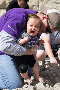 Evelyn Zender, 9-month-old Manhattan resident, reacts as her dad, Andrew Zender, editor of the K-stater magazine, places her feet in clay for the first time.  The second annual Clay Stomp was held Saturday, Sept. 28, 2013 from 10am to 3pm outside of Willard Hall. All K-students were welcome to come with their barefeet to mix 4,000 pounds of clay, which would later be bagged and used by art students.