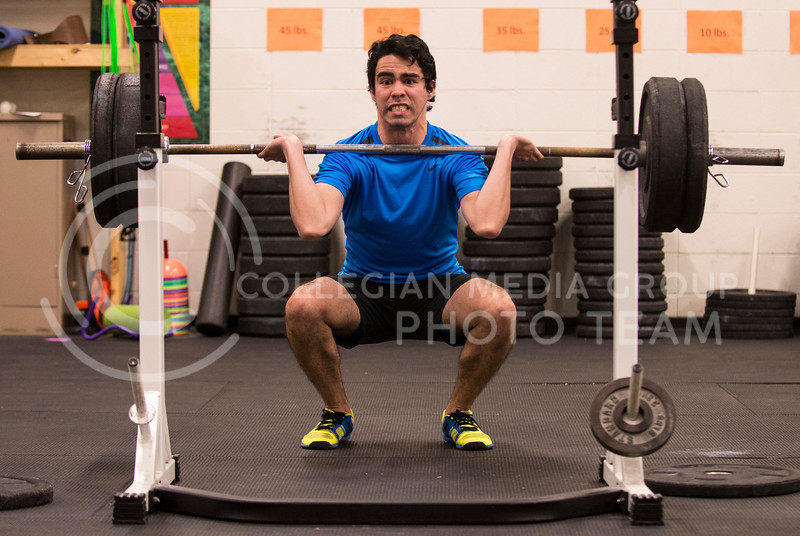 Jose Espinola, sophomore in bio-chemistry and German, struggles under the weight of 190 lbs while doing a front squat during a cross fit workout in the Natatorium on Feb. 20.