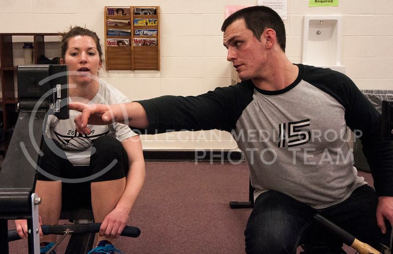Cross fit trainer Jake Frye, sophmore in kinesiology, instructs Manhattan resident Carly Meagher on the rowing machine during a cross fit work out in the Natatorium on Feb. 20.