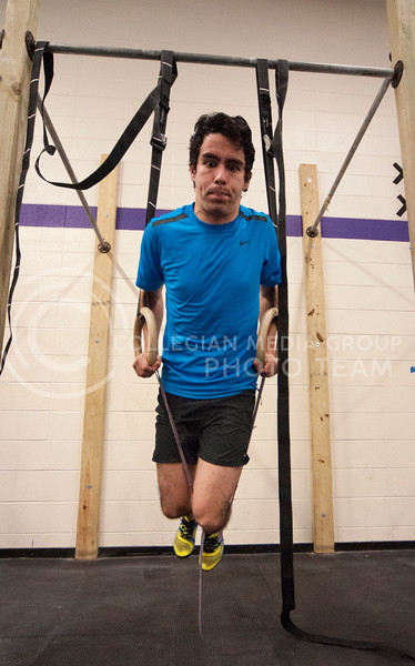Jose Espinola, sophomore in bio-chemistry and German, strains against the resistance of a rubber band while doing a ring dip during a cross fit workout in the Natatorium on Feb. 20.
