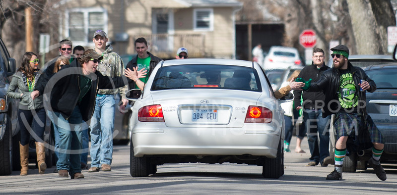 On their way to Aggieville a crowd of partiers high five the occpants of a passing car on the afternoon of Fake Patty's Day, Saturday, March 8.