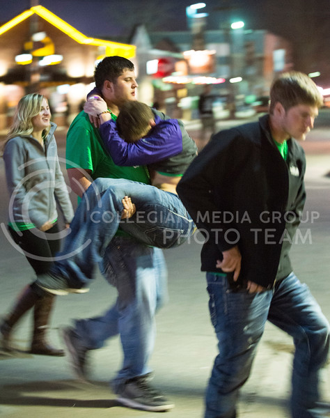 A Fake Patty's Day particpant carries his friend as their group exits Eighteen 63 and heads out of Aggieville on Saturday night.