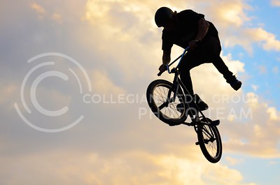 Eric Trombley, a BMX stunt rider, does a trick midair during the Rise Above BMX team's stop at Bosco Student Plaza Friday evening for the UPC After Hours. A dance party followed the show after the sun set.