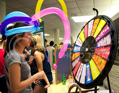 """Liping Zheng, freshman in hospitality management and dietetics, spins the """"wheel of fortune"""" at the McCain Ambassadors table at the Union Expo and Activities Carnival on August 29.  The Student Union was packed with K-State students signing up for various clubs and organizations and snagging free candy along the way."""