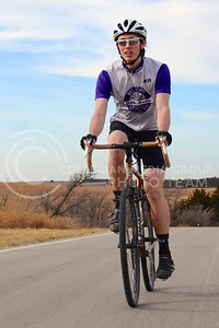 Chris Davis, sophomore in geography, charges up a hill on Deep Creek Road on an unusually warm and nice day, perfect for being active outside, on December 18. Davis, who also works at Big Poppi Bicycle Co. in Aggieville, loves to ride his road and mountain bikes to stay fit.
