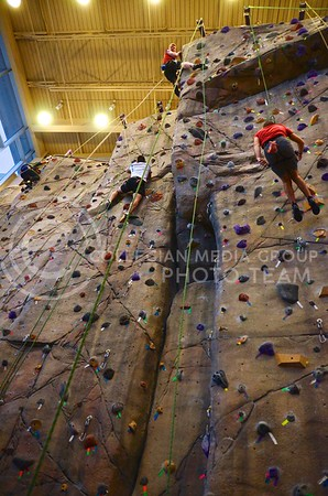 K-State students use all their strength to oppose gravity and pull themselves to the top of the rock wall at the Peters Recreation Complex December 17.
