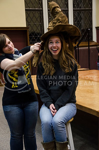 Sarah Merwin, junior studying public relations, grins in anticipation as Katie Harrison, sophomore studying secondary education in English, places the sorting hat on her head at the Harry Potter back to school dinner in the Great Room in Hale Library on Saturday.