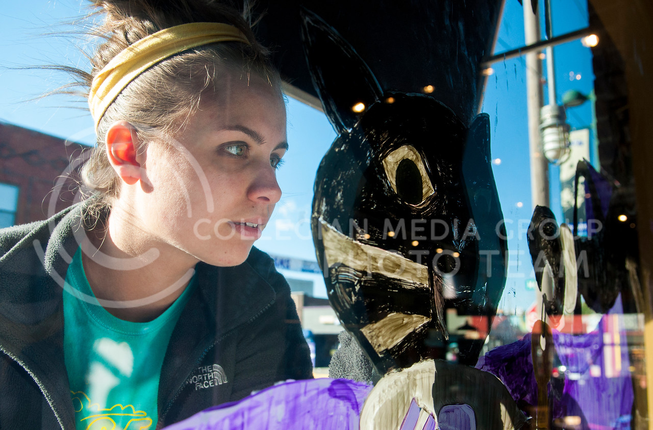 Kelsey Nelson, senior in accounting, adds detail to the Powercat Motorsports window painting on Oct. 22, in Aggieville.