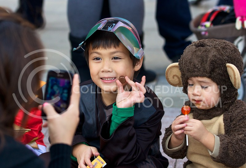 Ody Naylor (left), dressed as a bounty hunter in Star Wars, smiles as his mother snaps a few photos of him and his brother, Agam, as they wait for the K-State homecoming parade to pass through Aggieville on October 25, 2013.