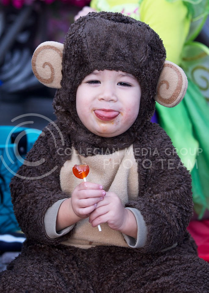 Two year old Agam Naylor makes monkey sounds as he enjoys his lolly pop that he got from Trick-or-Treat in Aggieville on October 25, 2013.