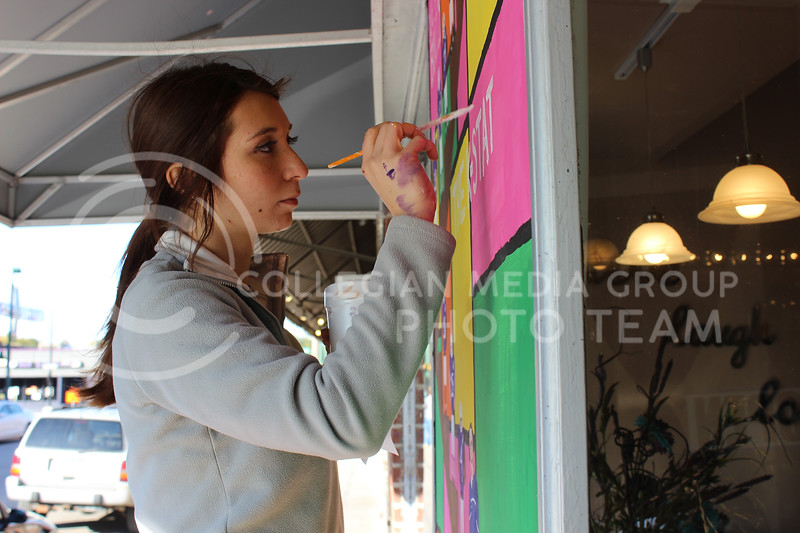 """Junior Laila Sammur works on a window painting of the Kansas State football team for the homecoming """"Paint the VIlle"""" event.  The greek houses who collaborated on this painting were Delta Delta Delta, Phi Delta Theta, and Sigma Pi."""