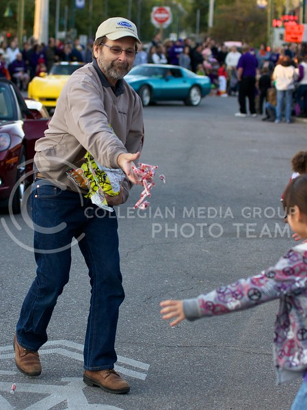 The man driving a red corvette during the K-State Homecoming Parade, stops in Aggieville to give out candy to kids lined up along the sidewalks on October 25, 2013.