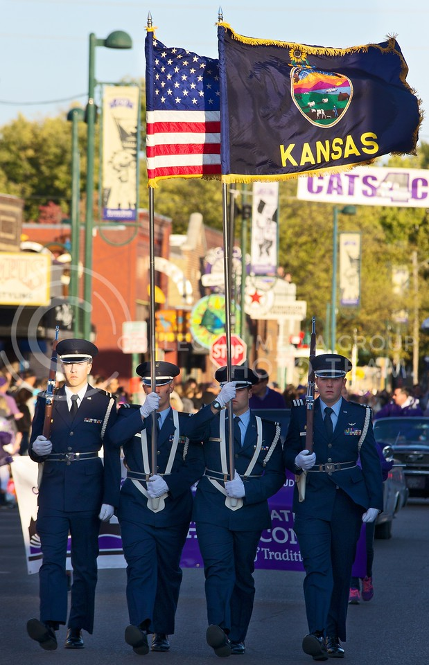 Leading the way, the American and Kansas flag wave in the breeze, as the 2013 K-State Homecoming parade passes through Aggieville on October 25, 2013.