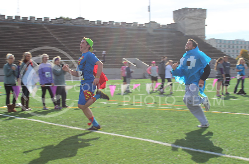 Tate Anderson and friend sprint across Memorial Stadium to the finish line of the Homecoming 5K.