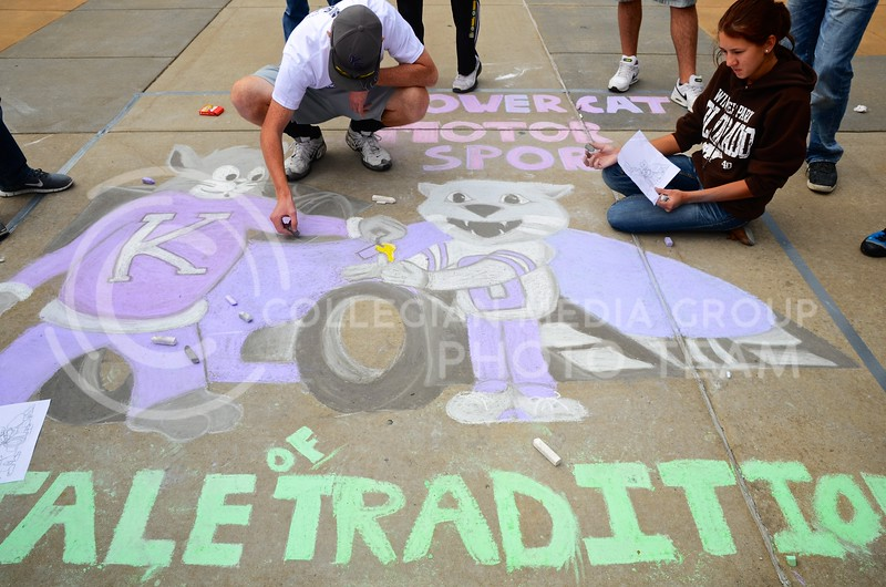 """Brett Cook and Victoria Voigt, both sophomores in mechanical engineering, put the finishing touches on the Powercat Motor Sports design team's sidewalk art during the Homecoming Sidewalk Chalking contest Sunday afternoon in Bosco Plaza. The theme for this year's Homecoming is """"A Tale of Tradition,"""" which designers could interpret however they saw fit in their designs."""