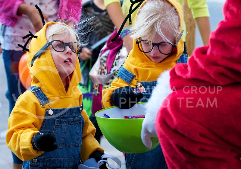 Dressed up as minions, sisters Halley (right) and Karli (left) Hutchinson pick out candy from Santa's pile during Trick-or-Treat in Aggieville on October 25, 2013.