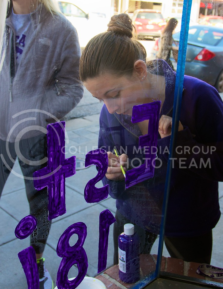 Alyssa Loper, sophomore in pre-nursing, adds another layer of paint to the glass panel of Subway at Aggieville as part of this years Paint the 'Ville on Tuesday.