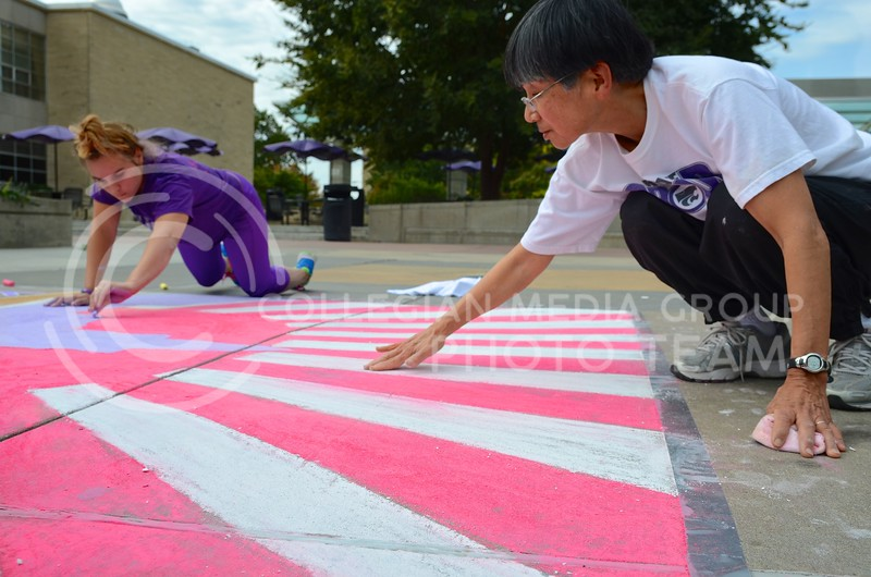 """Jennifer Stawski, sophomore in athletic training, and Barbara Johnson, director of the K-State Japanese Yosakoi Dance Club, smooth the chalk on the club's chalk art, featuring the rising sun behind Anderson Hall, during the Homecoming Sidewalk Chalking contest Sunday afternoon in Bosco Plaza. The theme for this year's Homecoming is """"A Tale of Tradition,"""" which designers could interpret however they saw fit in their designs."""