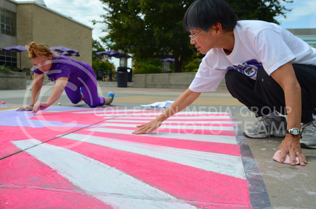 "Jennifer Stawski, sophomore in athletic training, and Barbara Johnson, director of the K-State Japanese Yosakoi Dance Club, smooth the chalk on the club's chalk art, featuring the rising sun behind Anderson Hall, during the Homecoming Sidewalk Chalking contest Sunday afternoon in Bosco Plaza. The theme for this year's Homecoming is ""A Tale of Tradition,"" which designers could interpret however they saw fit in their designs."